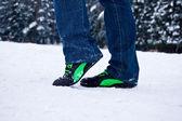 Dívka v džínách náklady na sněhu — Stock fotografie