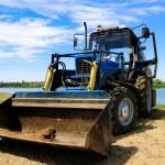 Bulldozer at sandy riverside against blue sky — Stock Photo #1040621
