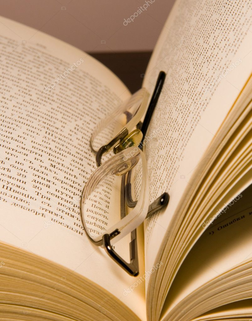 Glasses for reading and opened old book on a table — Stock Photo #1023404