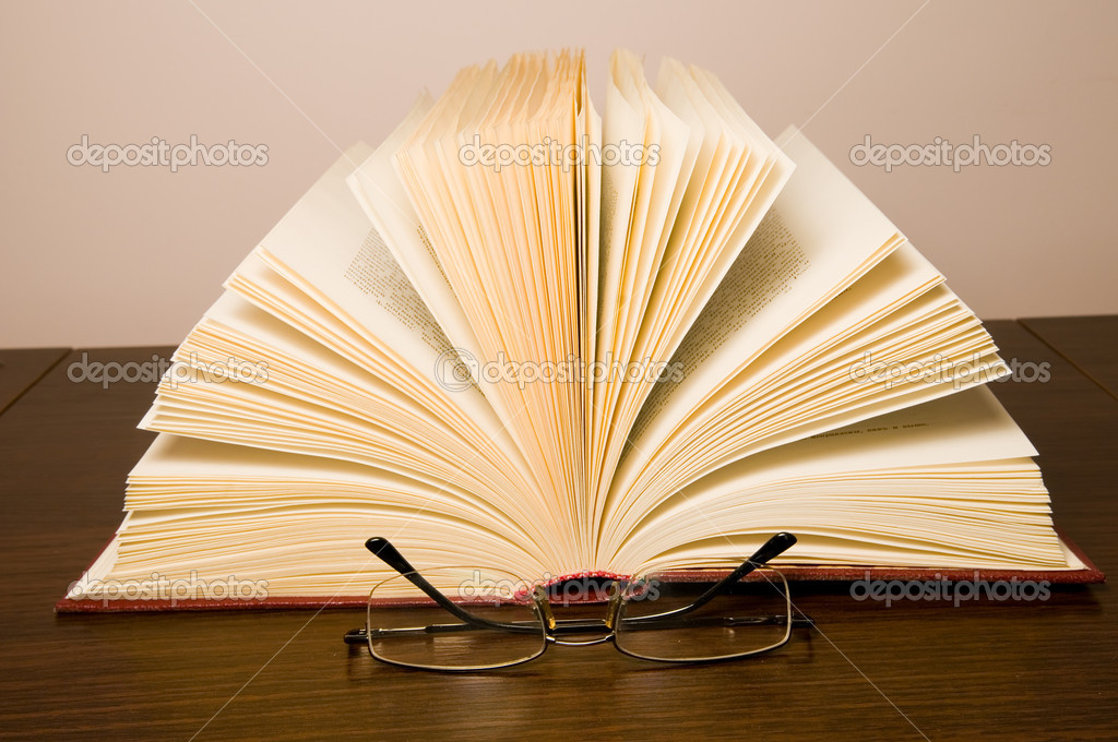 Glasses for reading and opened old book on a table — Stock Photo #1023424