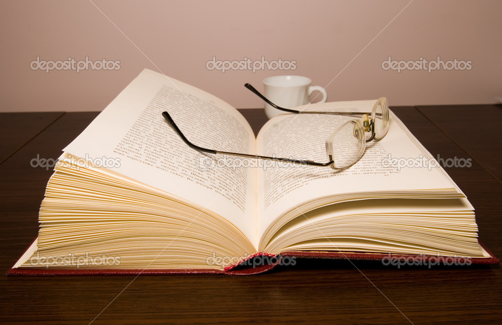 Glasses for reading and opened old book on a table, after a book white cup — Stock Photo #1023478
