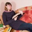 Royalty-Free Stock Photo: The girl with books on a sofa