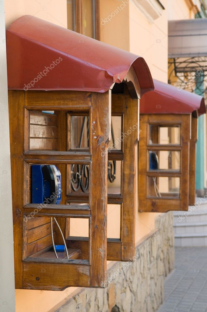 Two wooden pay phones in the street an old city — Stock Photo #1048429