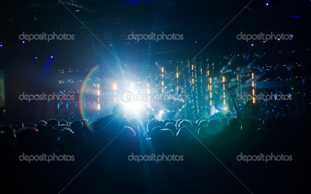 Silhouettes of against a scene and concert illumination. — Stock Photo #1573940