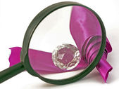 Magnifying and adornment with ribbon — Stock Photo