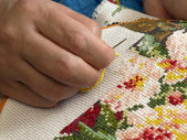 Female hand embroider at cross — Stock Photo