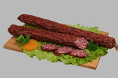 Smoked sausage on wooden board 2 — Stock Photo