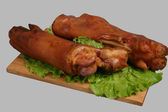 Smoked trotters on wooden board. — Stock Photo