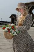 Girl with basket of flowers — Stock Photo