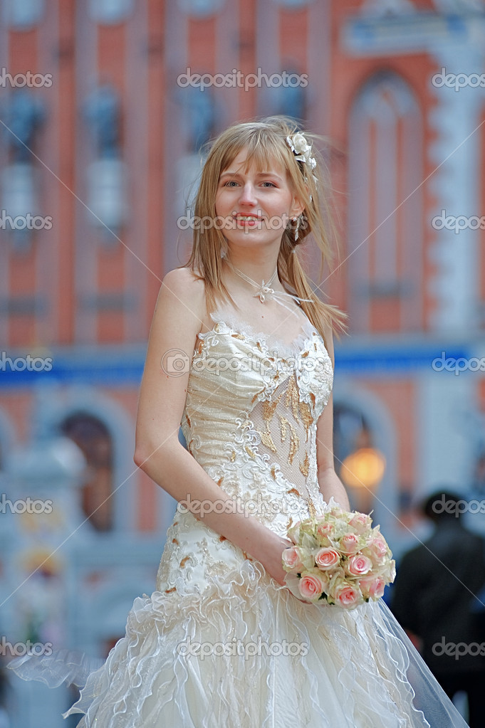 Bride in light dress with cream-colour rose bouquet in her hands and white flowers in her hair. — Stock Photo #1015054