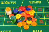 Large group of chips on green baize — Stock Photo