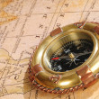 Old-fashioned compass on an age-old map — Stock Photo