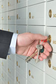 Hand with keys opening a deposit cell — Stock Photo