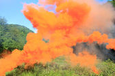 Orange smoke above a mountain glade — Stockfoto