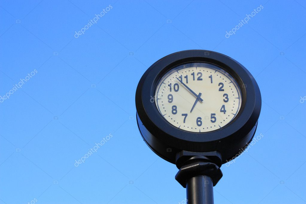 Arrow street clock on a background of blue sky — Stock Photo #1033604