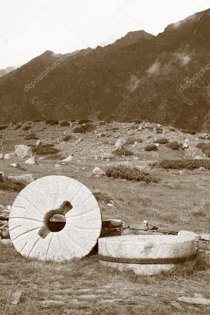 Two old millstone against the backdrop of mountain peaks — Stock Photo #1033823
