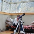 Стоковое фото: Girl looks through telescope