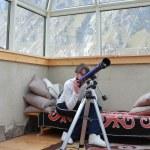 Girl looks through a telescope — Stock Photo