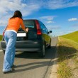 Woman pushing a car — Stock Photo
