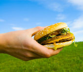 Hamburger in hand — Stock Photo