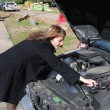 Stock Photo: Girl mending car
