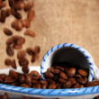 Cup, dish and falling beans of coffee — Stock Photo