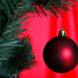 Christmas tree with ball against red bac - Stock Photo