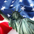图库照片: NY Statue of Liberty against a flag of U
