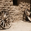 Old wheel from vintage cart beside wall - Stock Photo