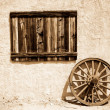 Royalty-Free Stock Photo: Old wooden plate and wheel beside wall