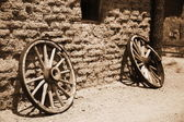 Old wheel from vintage cart beside wall — Stock Photo