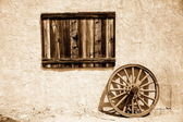 Old wooden plate and wheel beside wall — Stock Photo