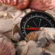 Compass with stones and mussels - Stock Photo