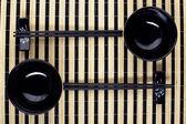Classical asian chopsticks and black bowls — Stock Photo