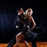 Dancers in ballroom against black — Stock Photo