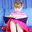 Girl reading book with apple at sofa — Stock Photo