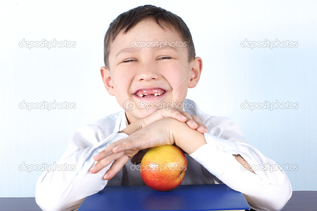 Smiling schoolboy without several tooths with red apple and book — Stock Photo #2372094
