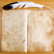 Old Book with feather pen on table — Stock Photo