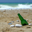 Bottle on sand near water — Stock Photo