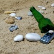 Bottle with cellular phone on sand — Stock Photo