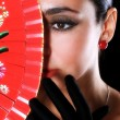 Latino woman with red fan — Stock Photo