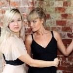 Two girls at old brick wall — Stock Photo
