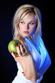 Girl with apple under blue light — Stock Photo