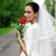 Bride in dress with red flower — Stock Photo #2678878
