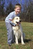 Boy with big retriever outdoors — Stock Photo