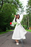 Bride with red flying flower at road — Stockfoto