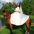 Bride horseback at horse — Stock fotografie