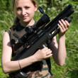 The girl with an air rifle. - Stock Photo