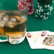 Counters of a card and a glass of whisky - Stock Photo