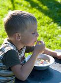 The boy eats wild strawberry. — Stock Photo